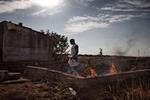 Michele Palazzi & Alessandro Penso: Migrant Worker Burning Garbage, Basilicata, Italy